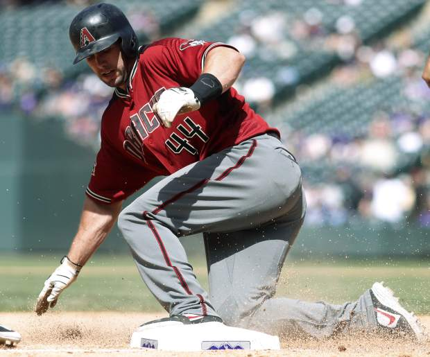 Arizona Diamondbacks' Paul Goldschmidt slides safely into third base after hitting a triple to drive in two runs off Colorado Rockies relief pitcher Jerry Vasto in the seventh inning of a baseball game Sunday, June 10, 2018, in Denver. Arizona won 8-3. (AP Photo/David Zalubowski)