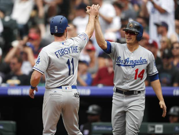 Los Angeles Dodgers' Logan Forsythe, left, is congratulated by Enrique Hernandez after they scored on a ground ball hit by pinch-hitter Breyvic Valera off Colorado Rockies relief pitcher Scott Oberg in the sixth inning of a baseball game Sunday, June 3, 2018, in Denver. Rockies shortstop Trevor Story was charged with a throwing error on the play. (AP Photo/David Zalubowski)