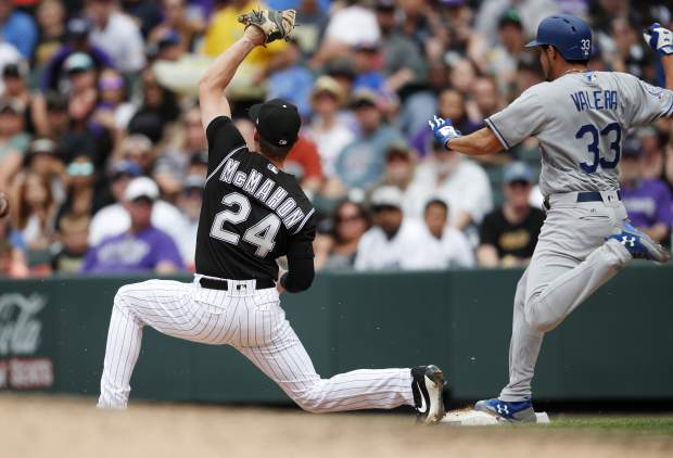 Colorado Rockies first baseman Ryan McMahon, left, has the throw from shortstop Trevor Story bounce away as Los Angeles Dodgers pinch-hitter Breyvic Valera (33) reaches first base safely in the sixth inning of a baseball game Sunday, June 3, 2018, in Denver. Two runs scored on the play. (AP Photo/David Zalubowski)