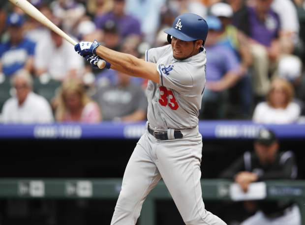 Los Angeles Dodgers pinch-hitter Breyvic Valera hits a ground ball to Colorado Rockies shortstop Trevor Story who committed a throwing error to allow in two run in the sixth inning of a baseball game Sunday, June 3, 2018, in Denver. (AP Photo/David Zalubowski)