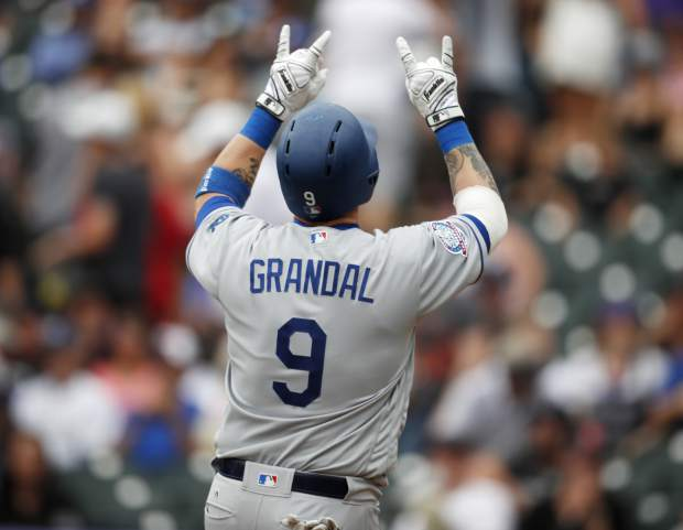 Los Angeles Dodgers' Yasmani Grandal gestures as he crosses home plate after hitting a two-run home run off Colorado Rockies relief pitcher Wade Davis in the ninth inning of a baseball game Sunday, June 3, 2018, in Denver. (AP Photo/David Zalubowski)