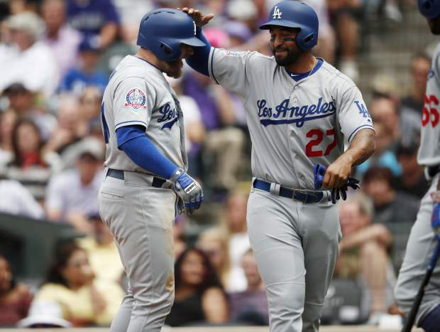 Los Angeles Dodgers' Matt Kemp, right, congratulates Max Muncy after his three-run home run off Colorado Rockies starting pitcher Chad Bettis in the third inning of a baseball game Sunday, June 3, 2018, in Denver. (AP Photo/David Zalubowski)