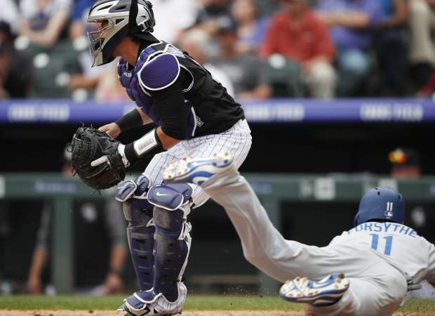 Colorado Rockies catcher Tony Wolters, left, looks for a throw as Los Angeles Dodgers' Logan Forsythe slides safely across home plate to score the go-ahead run on a ground ball hit by Justin Turner in the ninth inning of a baseball game Sunday, June 3, 2018, in Denver. (AP Photo/David Zalubowski)