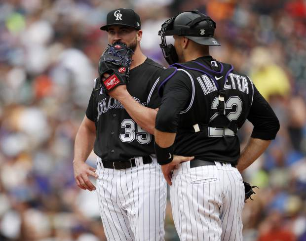 Colorado Rockies starting pitcher Chad Bettis, left, confers with catcher Chris Iannetta while waitingto be pulled form the mound after giving up a double to Los Angeles Dodgers' Yasiel Puig in the sixth inning of a baseball game Sunday, June 3, 2018, in Denver. (AP Photo/David Zalubowski)