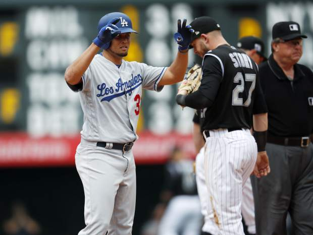 Los Angeles Dodgers pinch-hitter Breyvic Valera, left, gestures to the dugout after hitting a ground ball that Colorado Rockies shortstop Trevor Story, right, was charged with committing a throwing error to first base and allowing in two runs in the sixth inning of a baseball game Sunday, June 3, 2018, in Denver. (AP Photo/David Zalubowski)