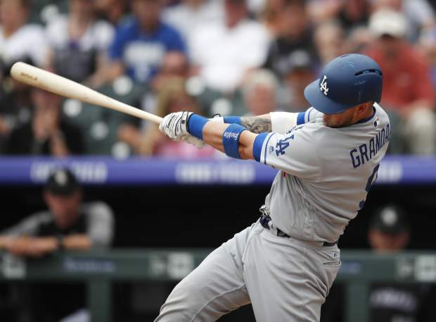 Los Angeles Dodgers' Yasmani Grandal follows through with his swing after connecting for a two-run home run off Colorado Rockies relief pitcher Wade Davis in the ninth inning of a baseball game Sunday, June 3, 2018, in Denver. (AP Photo/David Zalubowski)
