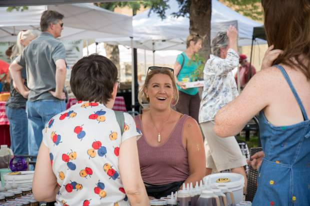 Melissa Maness with Colorado Mountain Honey helps customers at the Glenwood Springs Downtown Market. The annual market kicked off Tuesday night in Centennial Park and will continue to take place every Tuesday evening from 4 p.m. till dusk.