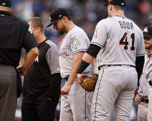 Miami Marlins starting pitcher Caleb Smith, center, is pulled from the mound after being checked for an injury in the second inning of a baseball game against the Colorado Rockies Sunday, June 24, 2018, in Denver. (AP Photo/David Zalubowski)