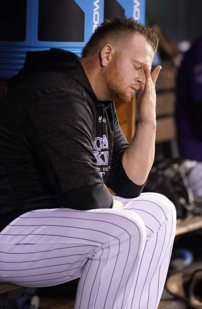 Colorado Rockies relief pitcher Brooks Pounders hangs his head in the dugout during the ninth inning of a baseball game against the New York Mets, Monday, June 18, 2018, in Denver. The Mets beat the Rockies 12-2. (AP Photo/Jack Dempsey)