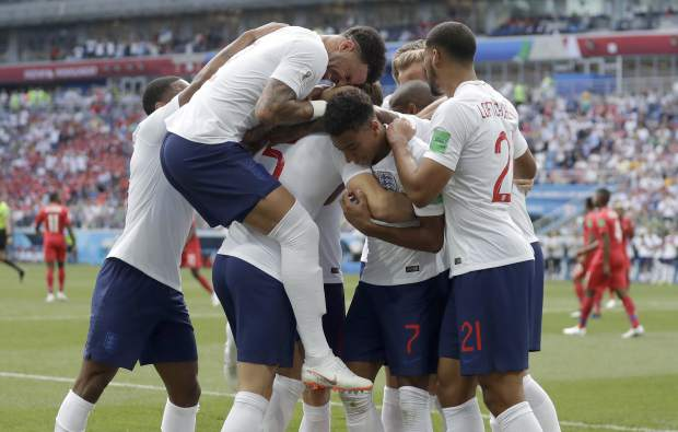 England players run to teammate John Stones after he scored his team's first goal during the group G match between England and Panama at the 2018 soccer World Cup at the Nizhny Novgorod Stadium in Nizhny Novgorod , Russia, Sunday, June 24, 2018. (AP Photo/Matthias Schrader)