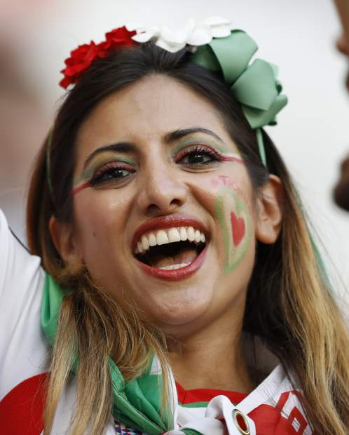 A woman supporter of Iran smiles for the camera as she waits for the start of the group B match between Iran and Portugal at the 2018 soccer World Cup at the Mordovia Arena in Saransk, Russia, Monday, June 25, 2018. (AP Photo/Francisco Seco)
