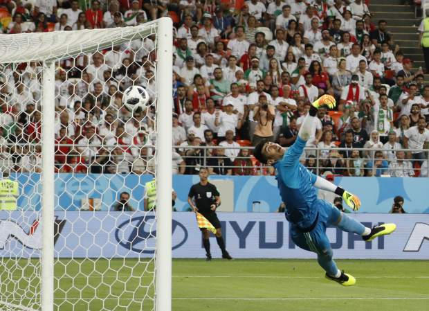 Iran goalkeeper Ali Beiranvand fails to stop Portugal's Ricardo Quaresma's opening goal during the group B match between Iran and Portugal at the 2018 soccer World Cup at the Mordovia Arena in Saransk, Russia, Monday, June 25, 2018. (AP Photo/Pavel Golovkin)