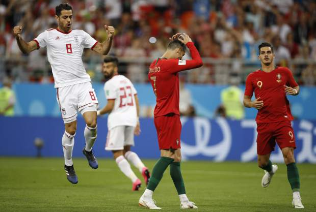Portugal's Cristiano Ronaldo, centre reacts after failing to score a penalty as Iran's Morteza Pouraliganji reavts, left, during the group B match between Iran and Portugal at the 2018 soccer World Cup at the Mordovia Arena in Saransk, Russia, Monday, June 25, 2018. (AP Photo/Francisco Seco)