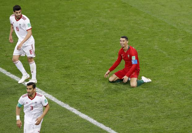 Portugal's Cristiano Ronaldo, right, reacts after receiving a foul by Iran's Saeid Ezatolahi, top left, during the group B match between Iran and Portugal at the 2018 soccer World Cup at the Mordovia Arena in Saransk, Russia, Monday, June 25, 2018. (AP Photo/Darko Bandic)