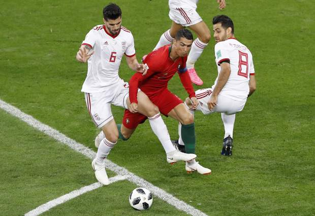 Portugal's Cristiano Ronaldo, bottom, is fouled by Iran's Saeid Ezatolahi to give away a penalty, during the group B match between Iran and Portugal at the 2018 soccer World Cup at the Mordovia Arena in Saransk, Russia, Monday, June 25, 2018. (AP Photo/Darko Bandic)