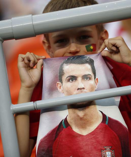 A young boy wears a shirt with a picture of Portugal's Cristiano Ronaldo on it as he waits for the start of the group B match between Iran and Portugal at the 2018 soccer World Cup at the Mordovia Arena in Saransk, Russia, Monday, June 25, 2018. (AP Photo/Francisco Seco)