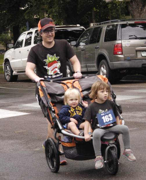 Matt Percy and his three young children, Emily, front, Henry, and Juniper (hidden behind Emily), were among the many fathers and their children taking in the annual Strawberry Shortcut for Father's Day on Sunday.