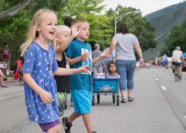Kids wait for candy and get sprayed with water during the 2018 Strawberry Days Parade on Saturday morning.