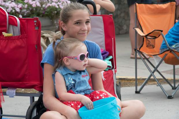 Two young girls watch the 2018 Strawberry Days Parade on Saturday morning.
