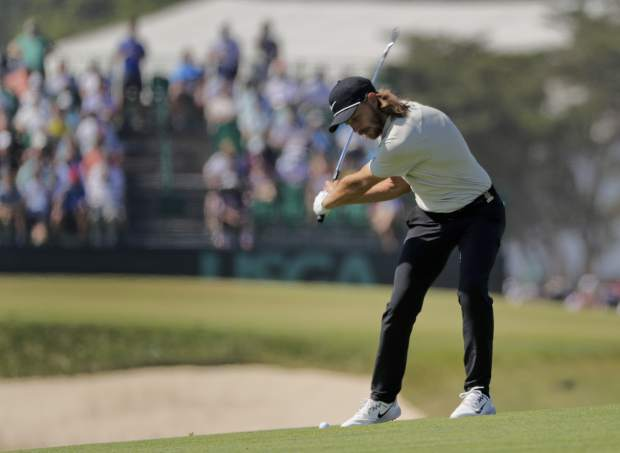 Tommy Fleetwood of England hits an approach shot on the 18th hole during the final round of the U.S. Open Golf Championship, Sunday, June 17, 2018, in Southampton, N.Y. (AP Photo/Frank Franklin II)
