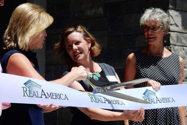 Ronda Weybright of RealAmerica maneuvers a large scissors Monday at the ribbon-cutting ceremony for the Roaring Fork Apartments in Basalt while assisted by Meghen Brown of the Colorado Housing and Finance Authority (center) and Basalt Mayor Jacque Whitsitt.