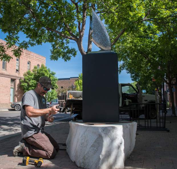 A town of Carbondale crew member works to install Ted Schaal's piece