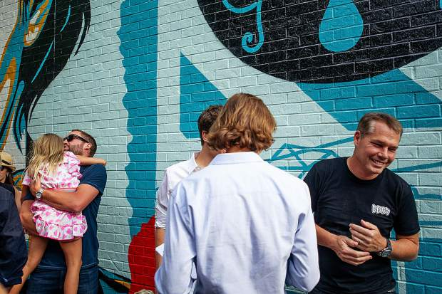 Artist Shepard Fairey, right, laughing with guests before the unveiling of his mural,