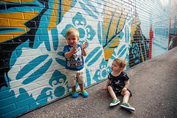 Bodhi Mancini, 17 months, and Emi Sloane-Brown in front of Shepard Fairey's mural behind Big Wrap after the unveiling Thursday night.