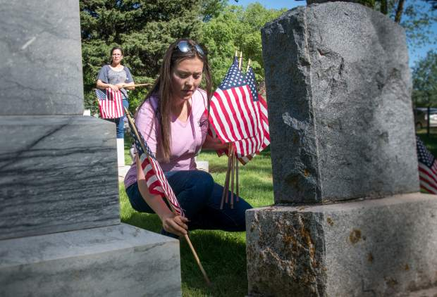2018 Miss Strawberry Days contestant Brittany Rhodes helps with placing the flags on the graves of veterans at Rosebud Cemetery in Glenwood Springs on Friday.