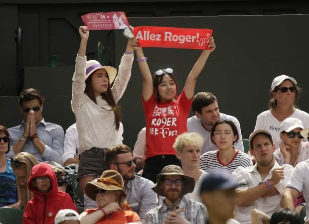 Fans of Switzerland's Roger Federer hold banners during his men's singles match against France's Adrian Mannarino, on day seven of the Wimbledon Tennis Championships, in London, Monday July 9, 2018. (AP Photo/Tim Ireland)