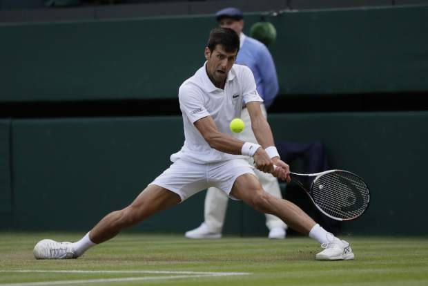 Novak Djokovic of Serbia returns a ball to Karen Khachanov of Russia during their men's singles match on the seventh day at the Wimbledon Tennis Championships in London, Monday July 9, 2018. (AP Photo/Kirsty Wigglesworth)