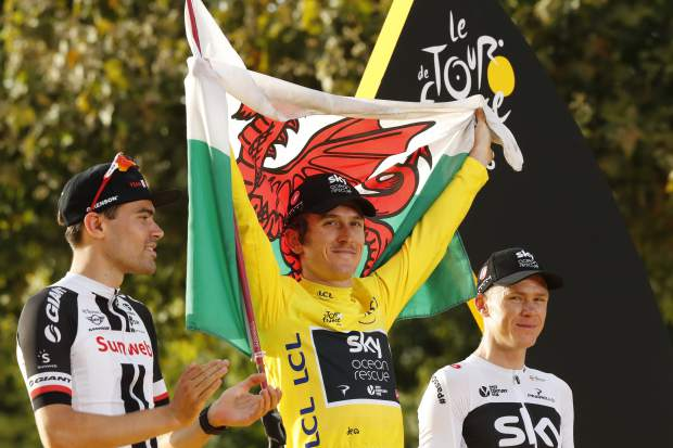 Tour de France winner Britain's Geraint Thomas, wearing the overall leader's yellow jersey celebrates on the podium with the Welsh flag as Netherlands' Tom Dumoulin, left,who placed second, and Britain's Chris Froome, who placed third, after the twenty-first stage of the Tour de France cycling race over 116 kilometers (72.1 miles) with start in Houilles and finish on Champs-Elysees avenue in Paris, Sunday July 29, 2018. (AP Photo/Laurent Rebours)
