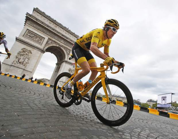 Tour de France winner Britain's Geraint Thomas, wearing the overall leader's yellow jersey, passes the Arc de Triomphe during the twenty-first stage of the Tour de France cycling race over 116 kilometers (72.1 miles) with start in Houilles and finish on Champs-Elysees avenue in Paris, France, Sunday July 29, 2018. (AP Photo/Christophe Ena)