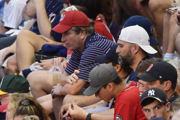 Supreme Court nominee Judge Brett Kavanuagh, in red hat, sits in the stands before the Major League Baseball All-star Game, Tuesday, July 17, 2018 in Washington. (AP Photo/Susan Walsh)