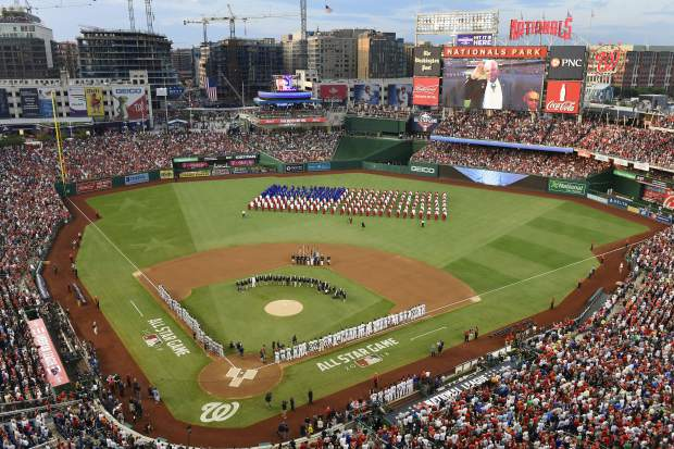 A choir moves on the field before the 89th MLB baseball All-Star Game, Tuesday, July 17, 2018, at Nationals Park, in Washington. (AP Photo/Susan Walsh)