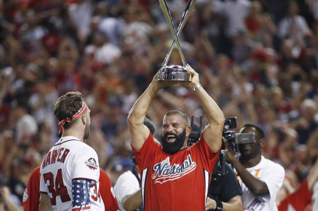 Ron Harper holds his son Washington Nationals Bryce Harper's trophy after the Major League Baseball Home Run Derby Monday, July 16, 2018, in Washington. (AP Photo/Patrick Semansky)