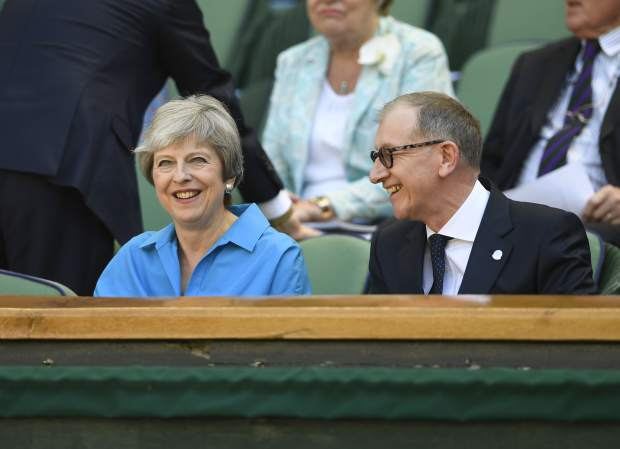 British Prime Minister Theresa May and her husband Philip May sit in the Royal Box on Centre Court during the men's singles final match between Novak Djokovic of Serbia and Kevin Anderson of South Africa at the Wimbledon Tennis Championships in London, Sunday July 15, 2018. (Neil Hall/Pool via AP)