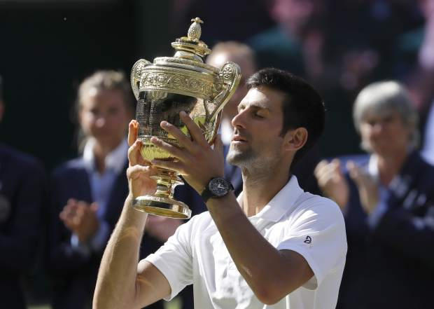 Serbia's Novak Djokovic lifts the trophy after winning the men's singles final match against Kevin Anderson of South Africa, at the Wimbledon Tennis Championships, in London, Sunday July 15, 2018.(AP Photo/Kirsty Wigglesworth)