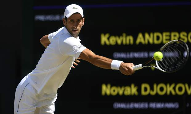 Novak Djokovic of Serbia returns the ball to Kevin Anderson of South Africa during the men's singles final match at the Wimbledon Tennis Championships in London, Sunday July 15, 2018. (Neil Hall/Pool via AP)