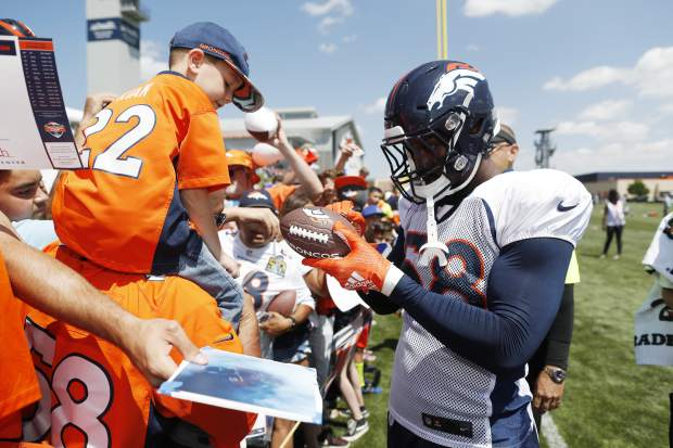 Denver Broncos linebacker Von Miller signs autographs for fans after drills at the team's NFL football training camp Monday, July 30, 2018, in Englewood, Colo. (AP Photo/David Zalubowski)