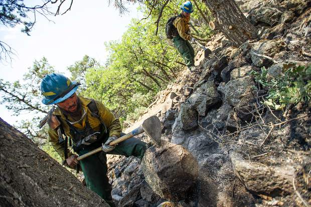 Oregon firefighters Markus Idroga, left, and Martin Sierra put out hot spots above the Wilds neighborhood in Basalt from the Lake Christine Fire on Sunday afternoon.