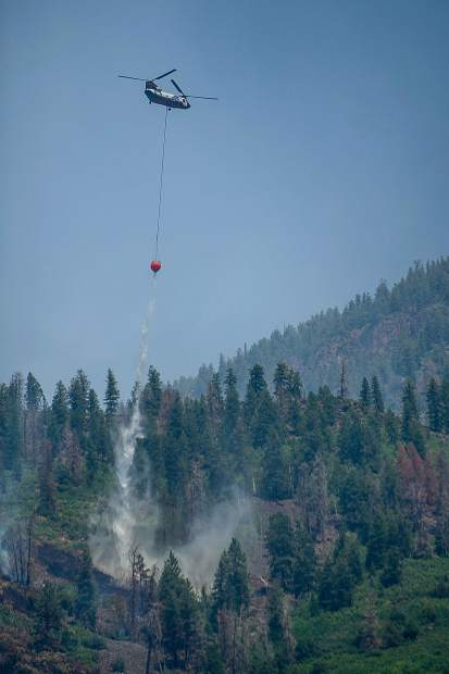 A Chinook helicopter drops a bucket of water on Basalt Mountain from Cedar Drive on Sunday afternoon.