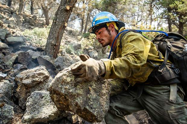 Oregon firefighter Ismael Corona moves rocks and puts out hot spots above the Wilds neighborhood in Basalt from the Lake Christine Fire on Sunday afternoon.