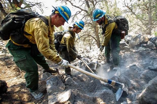From left, firefighters Martin Sierra, Ismael Corona and Martin Sierra put out Lake Christine Fire hot spots above the Wilds neighborhood in Basalt on Sunday afternoon.