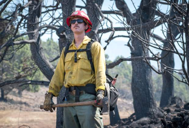 Washington state firefighter Garrett Gradillas assesses the charred landscape before heading out to help tackle the Lake Christine Fire on Monday morning.