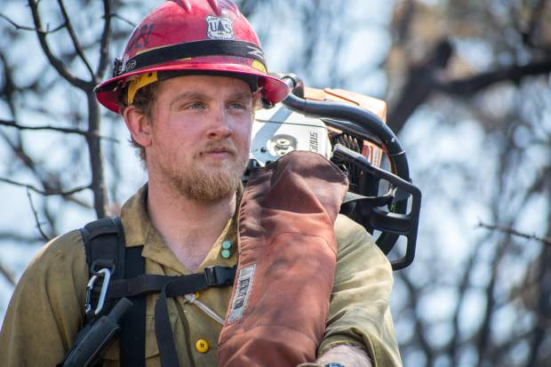 Washington state firefighter Tanner Mawhinney assesses the charred landscape before heading out to help tackle the Lake Christine Fire on Monday morning.