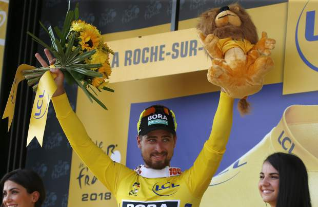Stage winner Slovakia's Peter Sagan, wearing the overall leader's yellow jersey, celebrates on the podium after the second stage of the Tour de France cycling race over 182.5 kilometers (113.4 miles) with start in Mouilleron-Saint-Germain and finish in La Roche Sur-Yon, France, Sunday, July 8, 2018. (AP Photo/Peter Dejong)