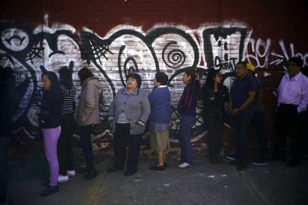 People wait to vote during general elections in Iztapalapa, Mexico City, Sunday, July 1, 2018. Sunday's elections for posts at every level of government are Mexico's largest ever and have become a referendum on corruption, graft and other tricks used to divert taxpayer money to officials' pockets and empty those of the country's poor. (AP Photo/Ramon Espinosa)