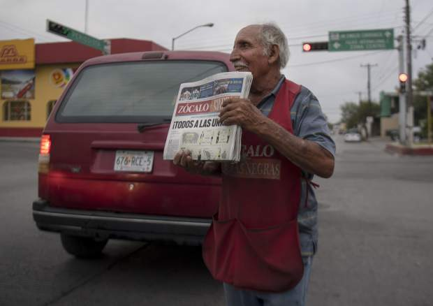 A vendor offers newspapers to cars stopped at a traffic light in Piedras Negras, Mexico, Sunday, July 1, 2018. Sunday's elections for posts at every level of government are Mexico's largest ever and have become a referendum on corruption, graft and other tricks used to divert taxpayer money to officials' pockets and empty those of the country's poor. Headline reads:
