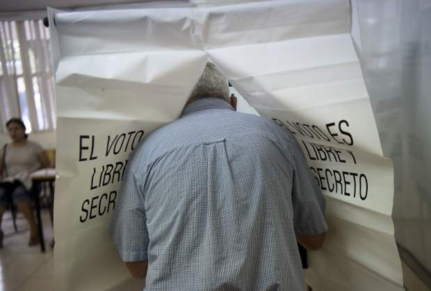 A man casts his vote at a polling station in Piedras Negras, Mexico, Sunday, July 1, 2018. Sunday's elections for posts at every level of government are Mexico's largest ever and have become a referendum on corruption, graft and other tricks used to divert taxpayer money to officials' pockets and empty those of the country's poor. (AP Photo/Nick Wagner)